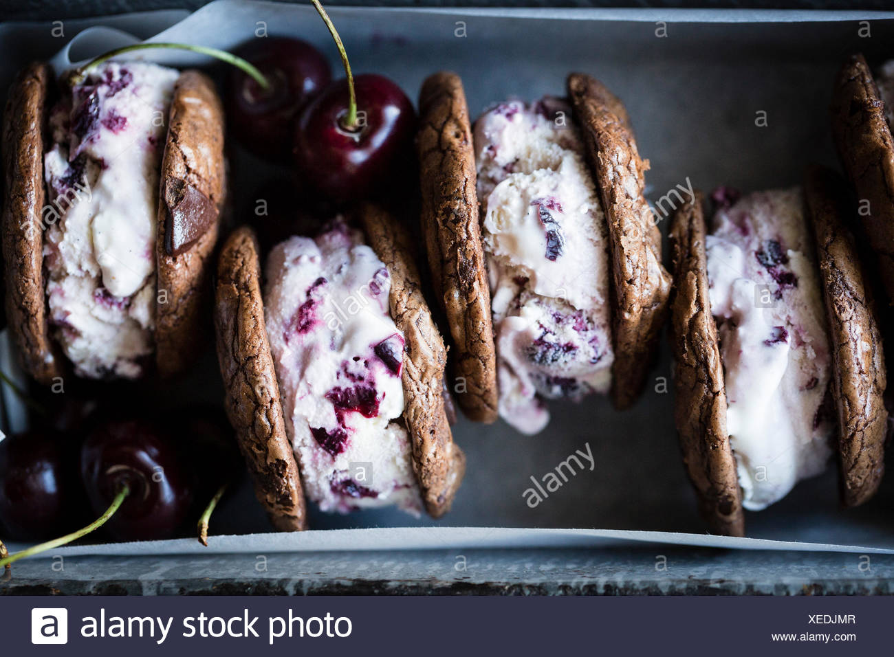 Roasted cherry ice cream sandwiches with salted double chocolate buckwheat cookies (gluten-free) - Stock Image