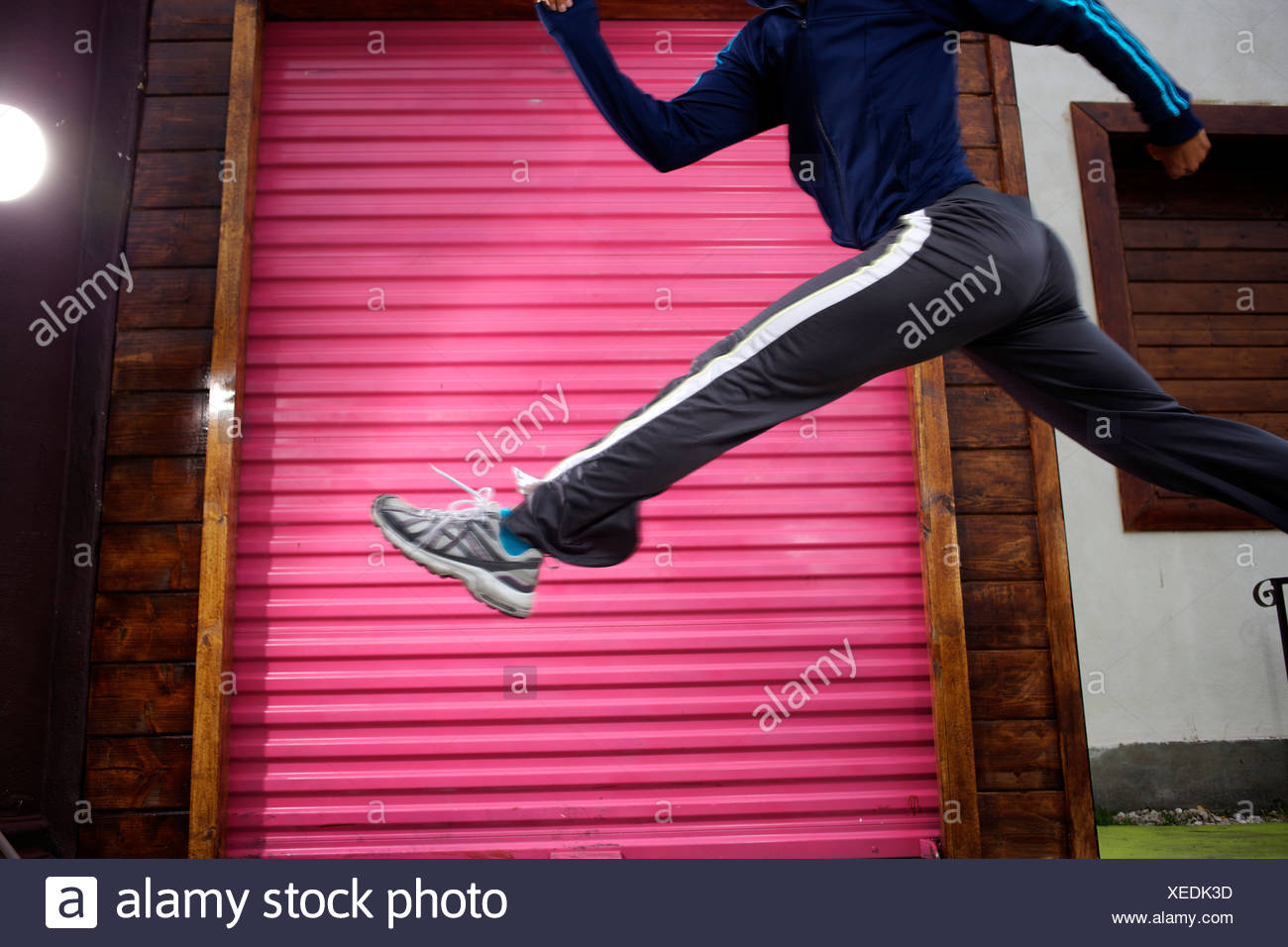 Legs and lower body of a female runner leaping with a pink door in the backgroud in San Diego. - Stock Image
