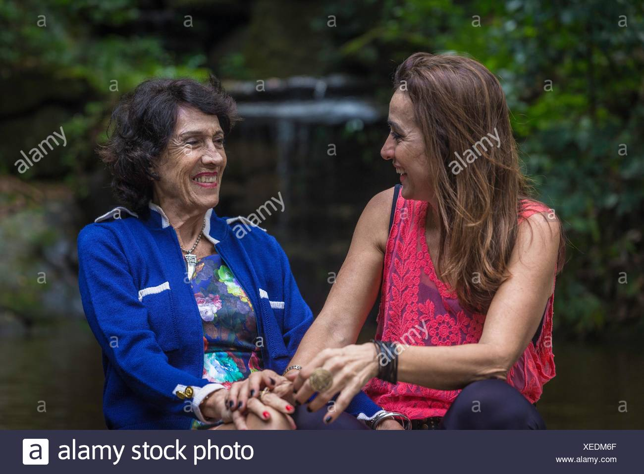 Mature woman and mother holding hands and laughing at woodland waterfall - Stock Image