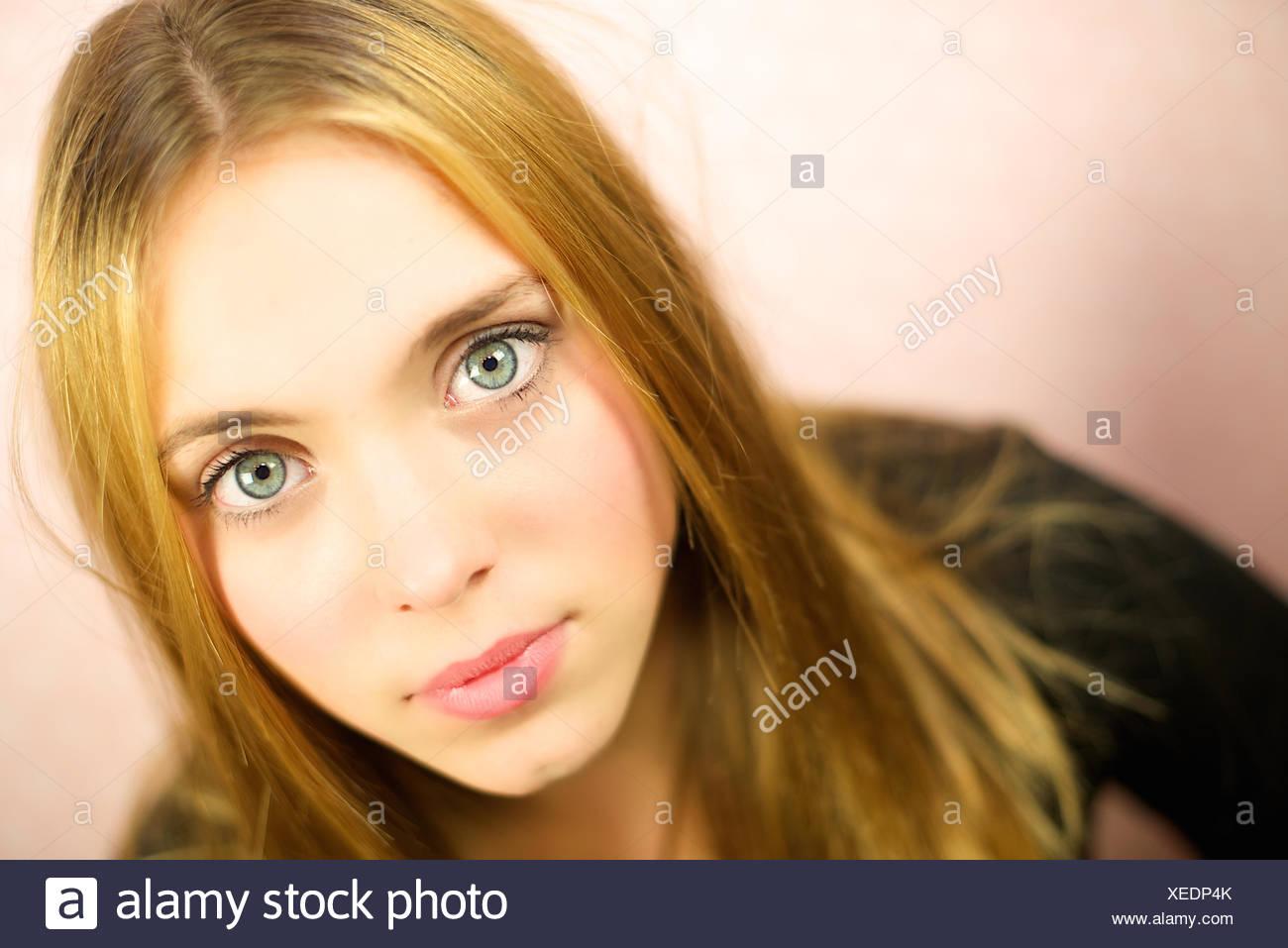 Portrait of girl (12-13) on beige background - Stock Image