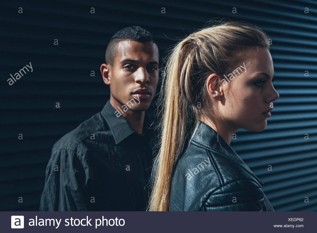 Black dressed young couple in front of black facade - Stock Image