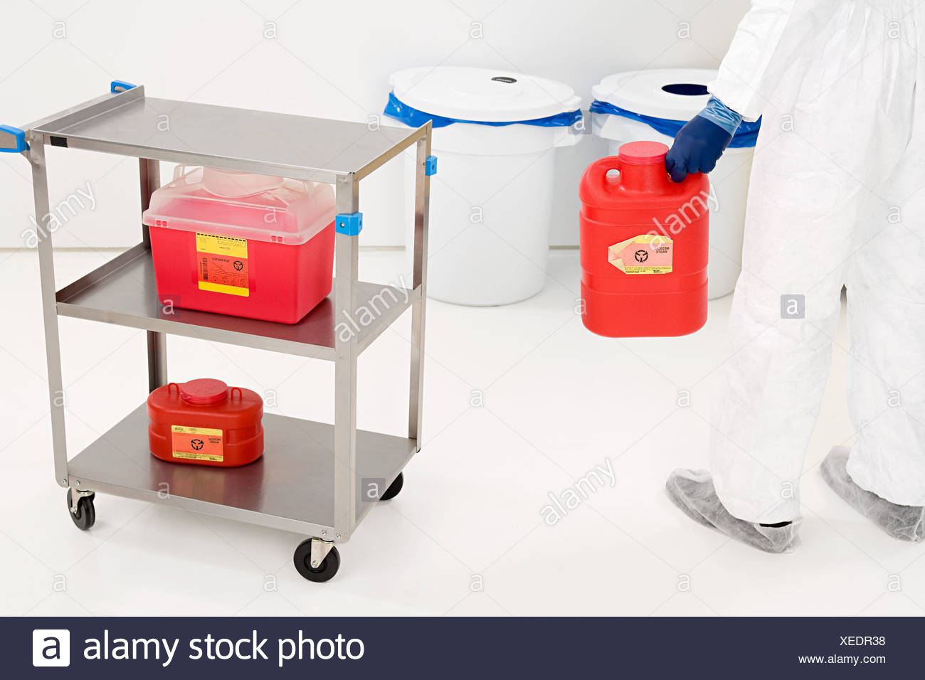 A scientist holding a container of chemical waste - Stock Image