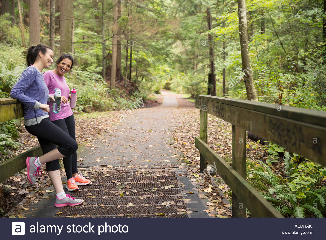 Mother and daughter water bottles taking break woods - Stock Image