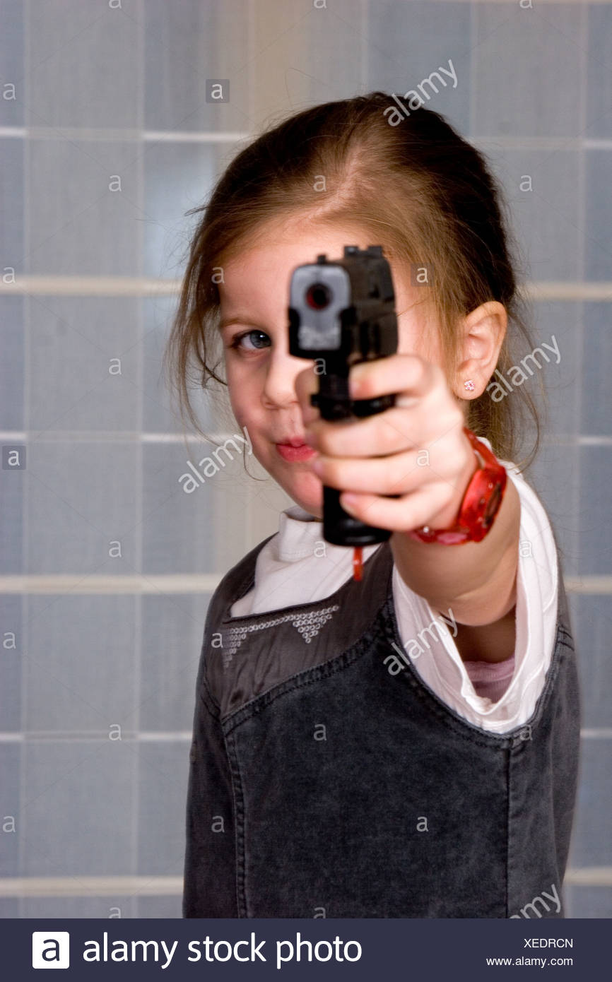 Concept of an aggressive young girl pointing gun towards the camera - Stock Image