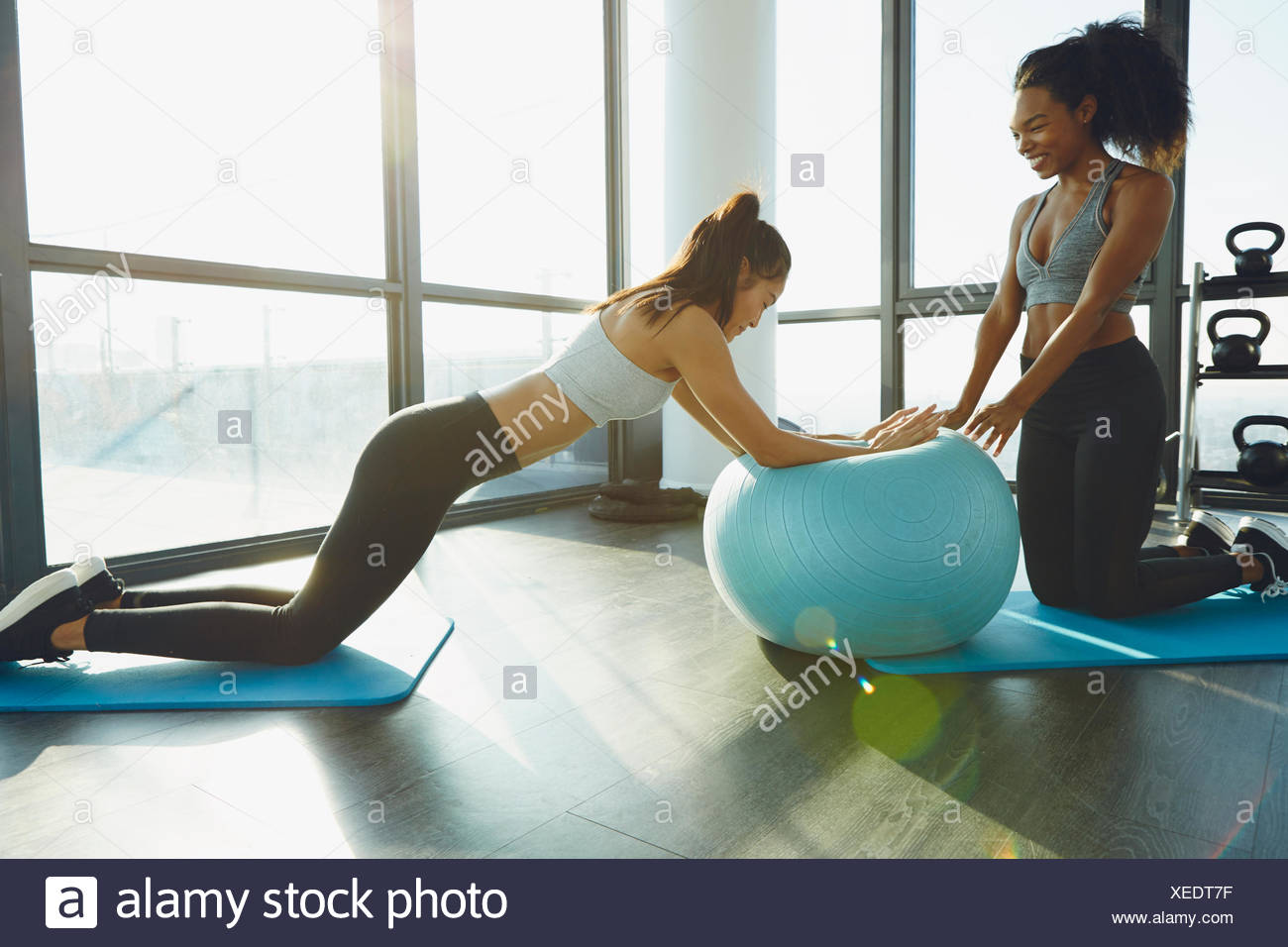 Two young women exercising in gym, using inflatable exercise ball - Stock Image