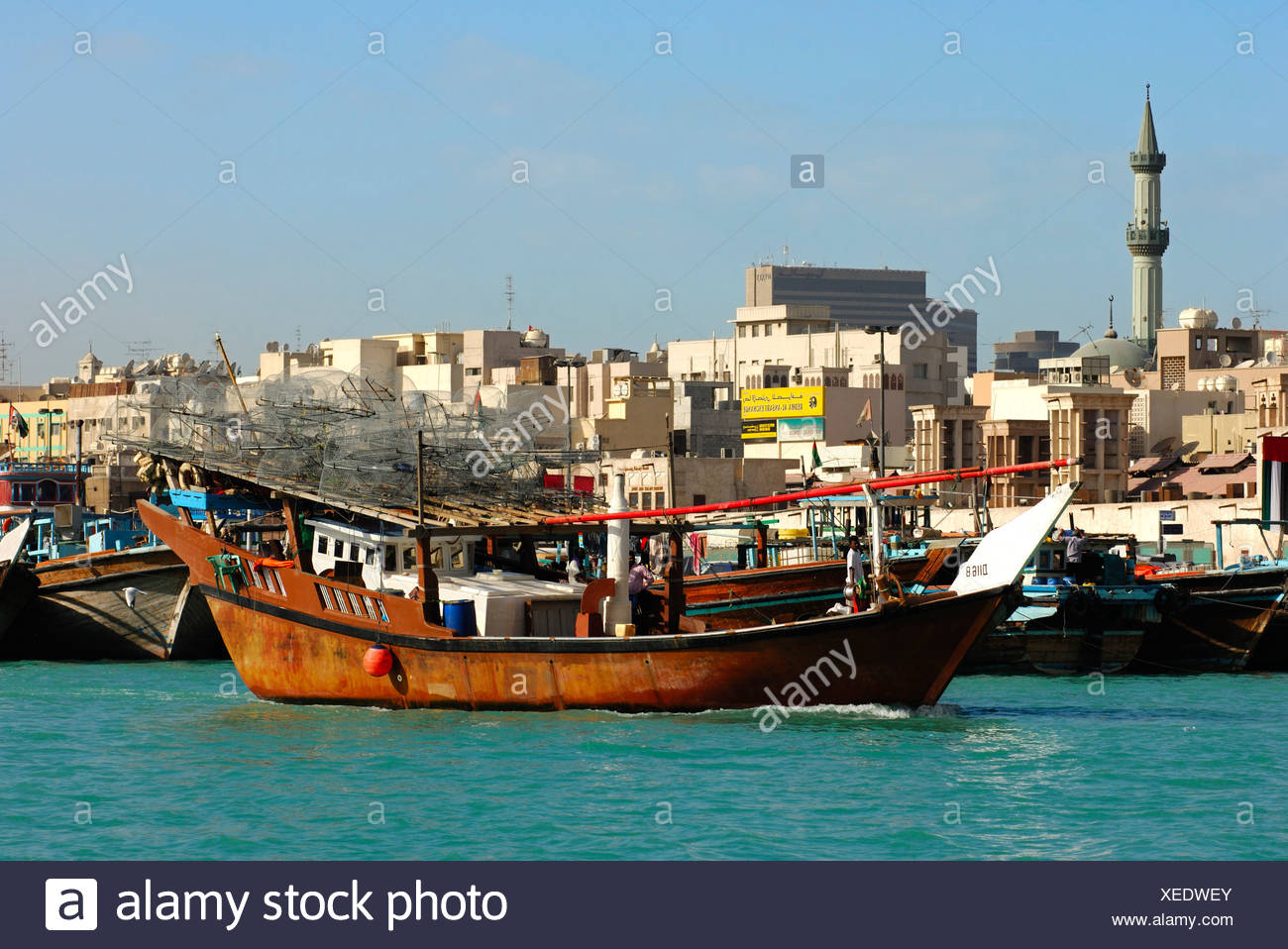 A traditional fisher boat heading out to fish loaded with bow nets in the Dubai Creek in front of the back-drop of the Deira di - Stock Image