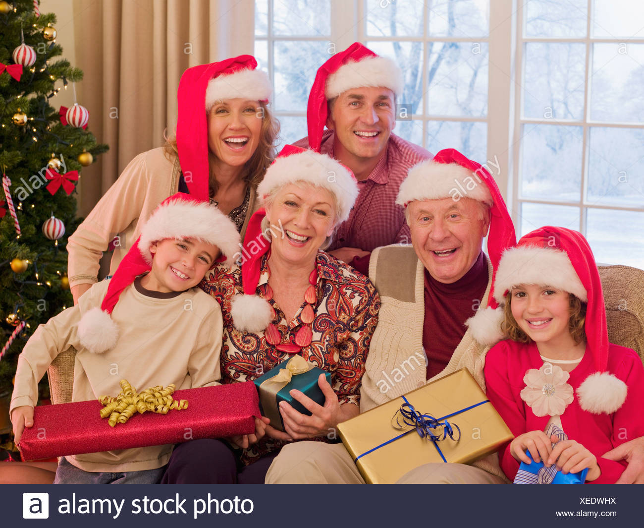 Multi-generation family wearing santa hats and holding Christmas ...