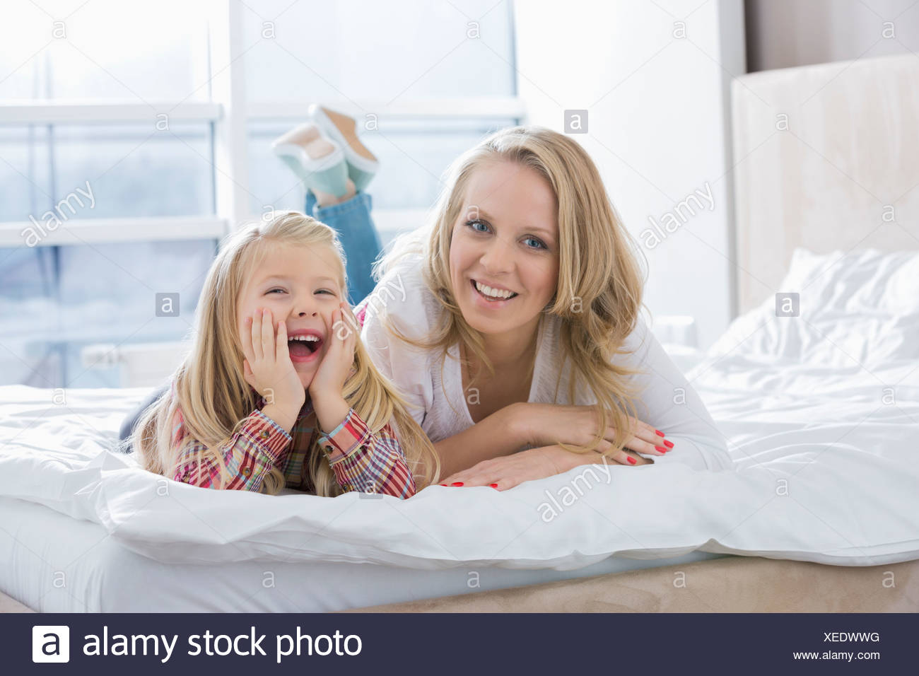Portrait of happy mother and daughter lying in bed - Stock Image
