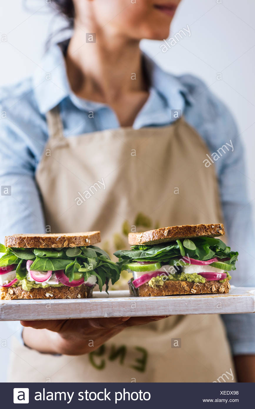 A woman with a blue shirt and a beige apron holding springtime feta sandwiches with herbs, avocado and pickled red onions on a white board photographe - Stock Image