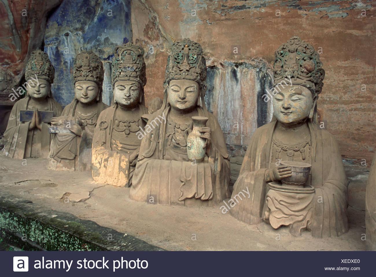 China, Sichuan, Dazu, Baoding Shan, Cave 11, Reclining Buddha, life-like busts of officials donors in meditation below Buddha - Stock Image
