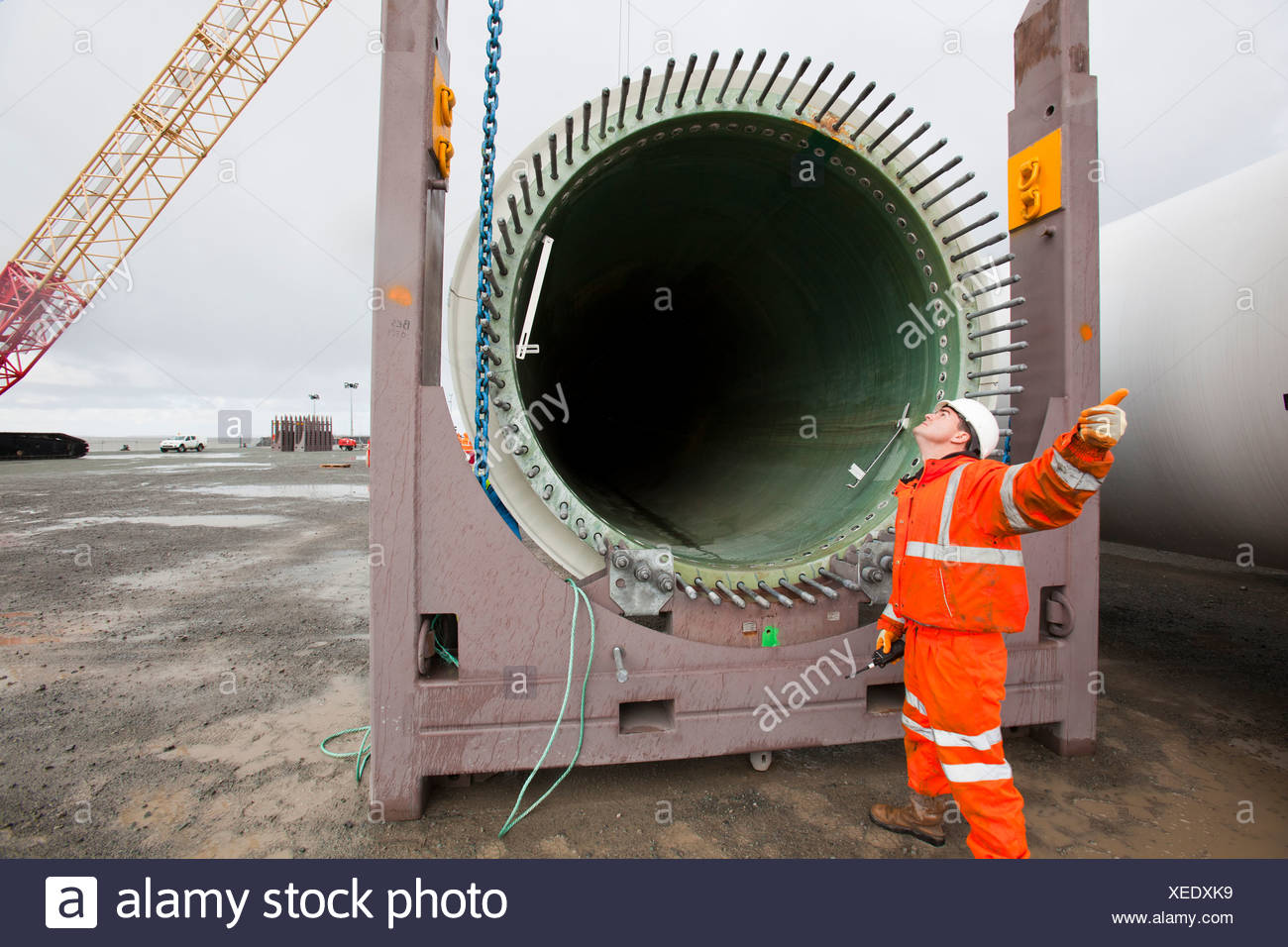 Workers prepare to lift a wind turbine blade onto a jack up barge for the Walney offshore wind farm, Cumbria, UK. - Stock Image