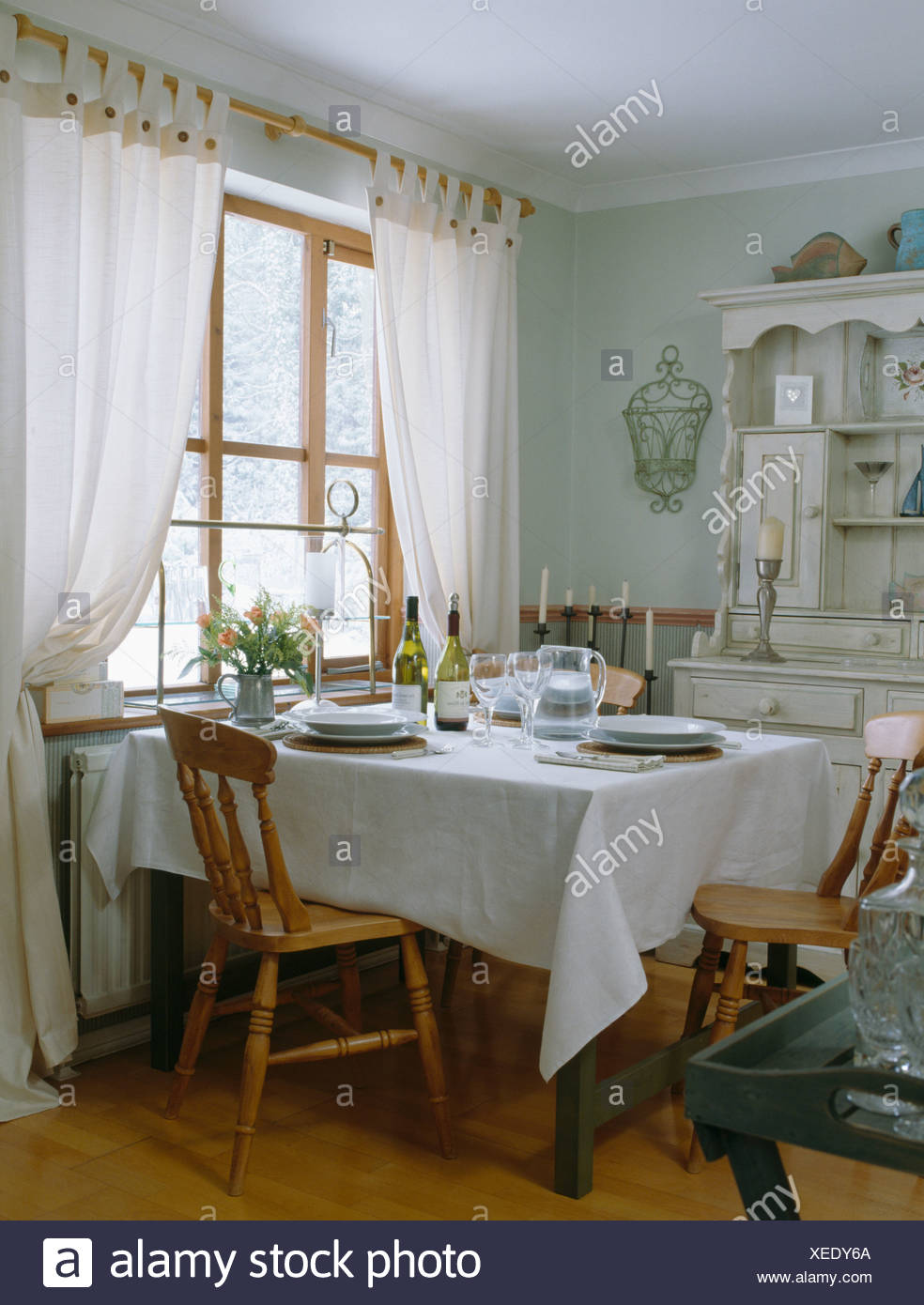 White Linen Cloth On Table With Simple Wooden Chairs In Pale Green Dining Room With White Curtains On Window Stock Photo Alamy