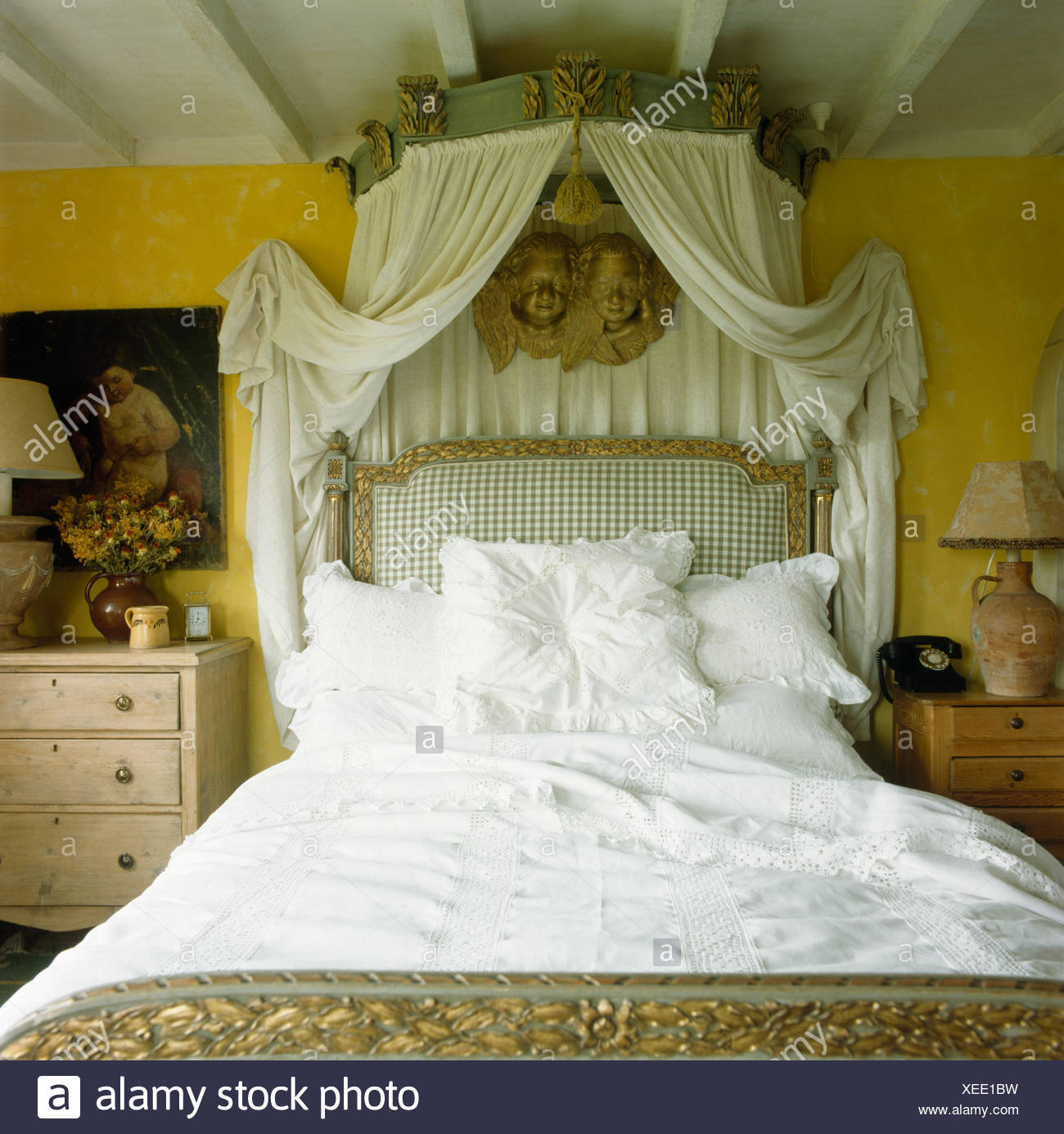 Ornate Canopy With White Drapes Above French Bed With White Bedlinen In  Eighties Bedroom   Stock