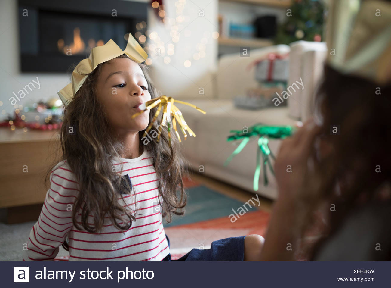 Sisters in paper Christmas crowns playing with party favors - Stock Image
