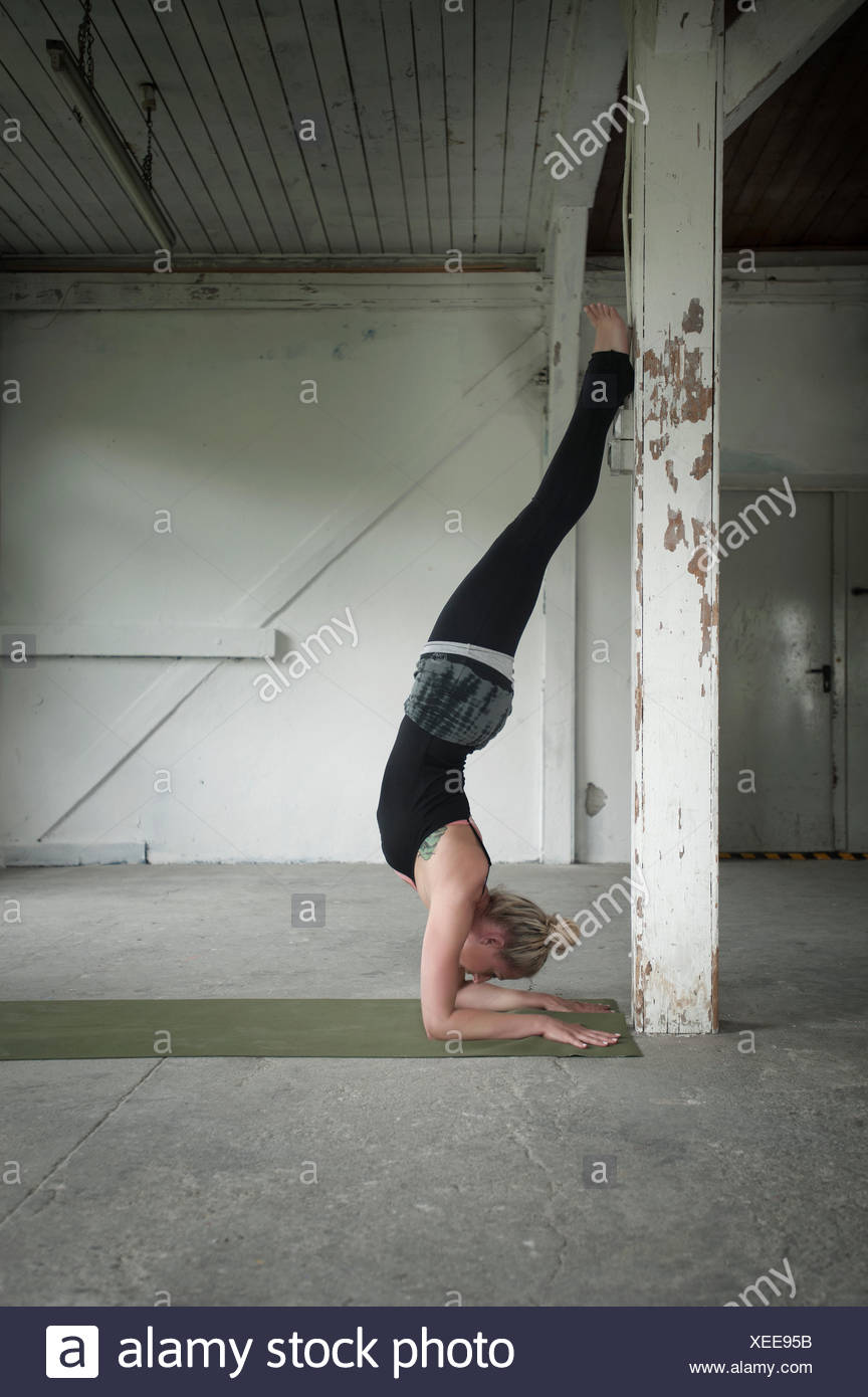 Mid adult woman practicing handstand in yoga studio, Munich, Bavaria, Germany - Stock Image