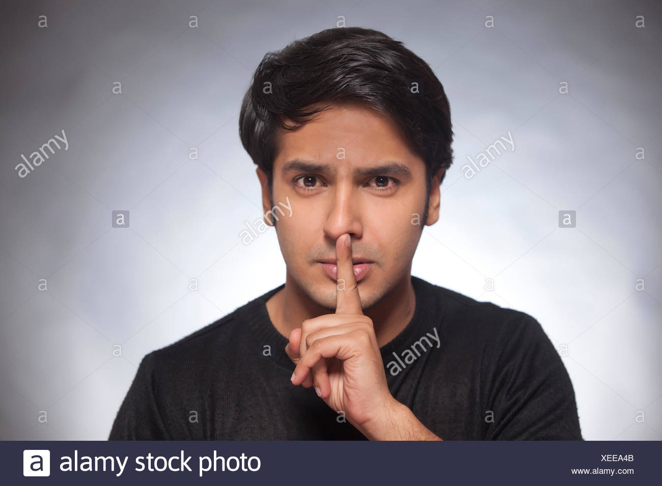 Portrait of a young man with his finger on lips - Stock Image