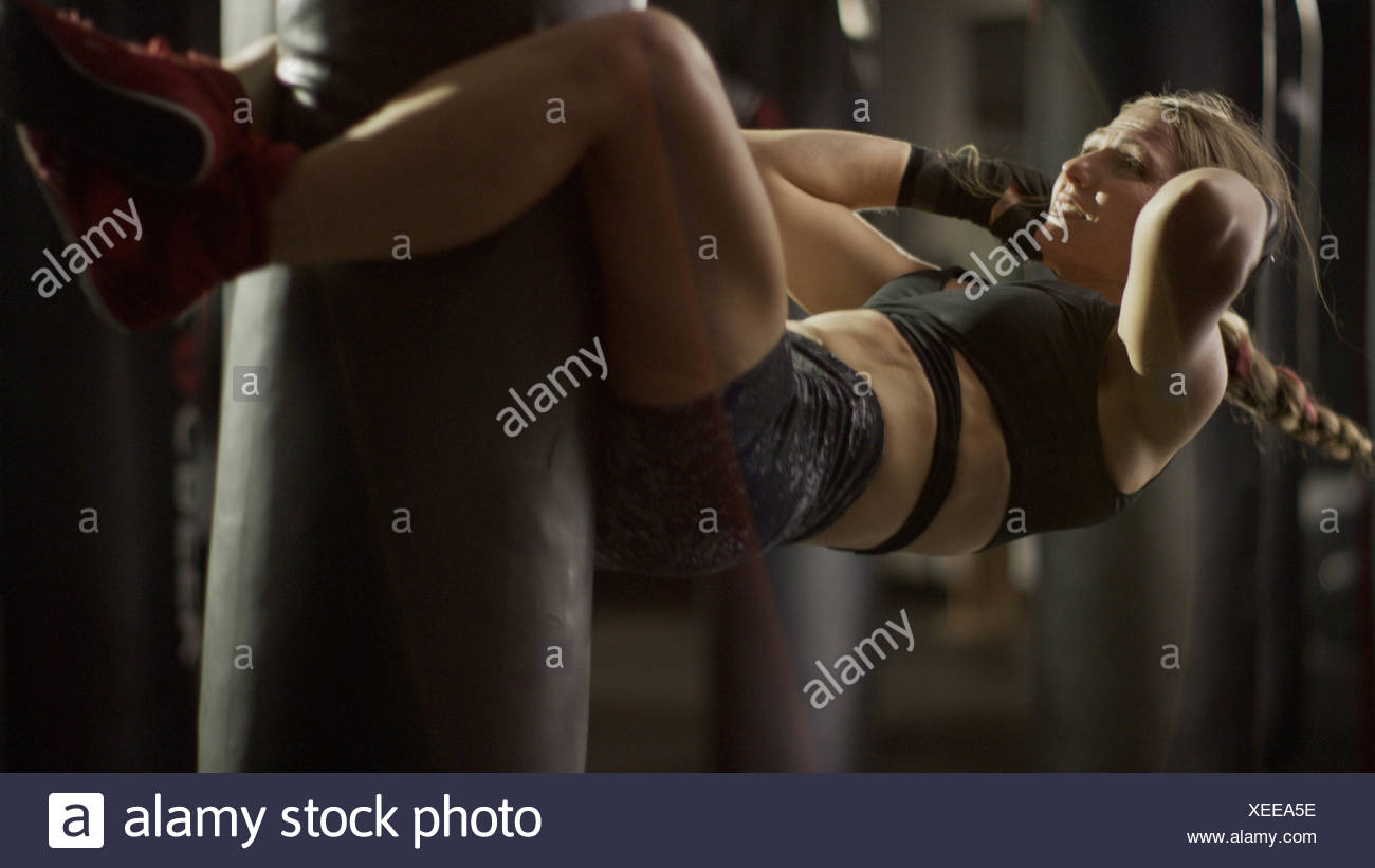Selective focus view of female boxer working out and doing sit-ups on punching bag in gym - Stock Image