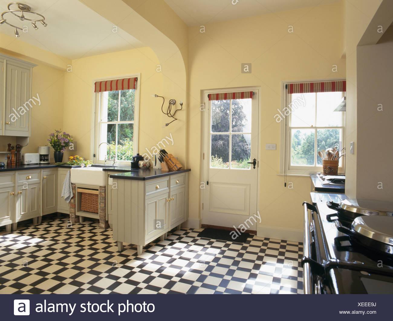 Black White Vinyl Flooring In Pastel Yellow Country Kitchen Stock Photo Alamy