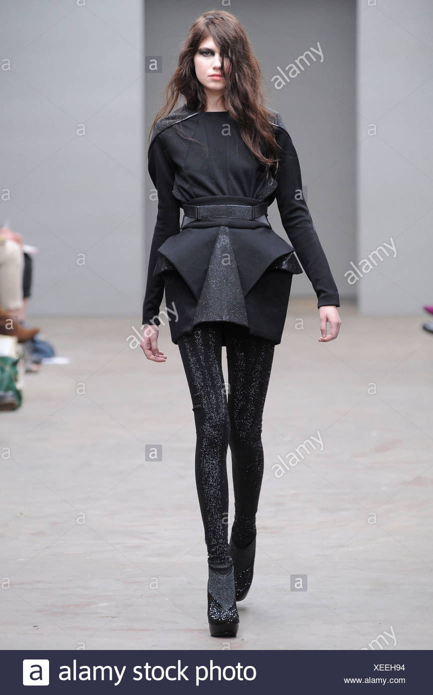 Black dress with long sleeves, geometrical ruffles, black tights and grey platform ankle boots - Stock Image