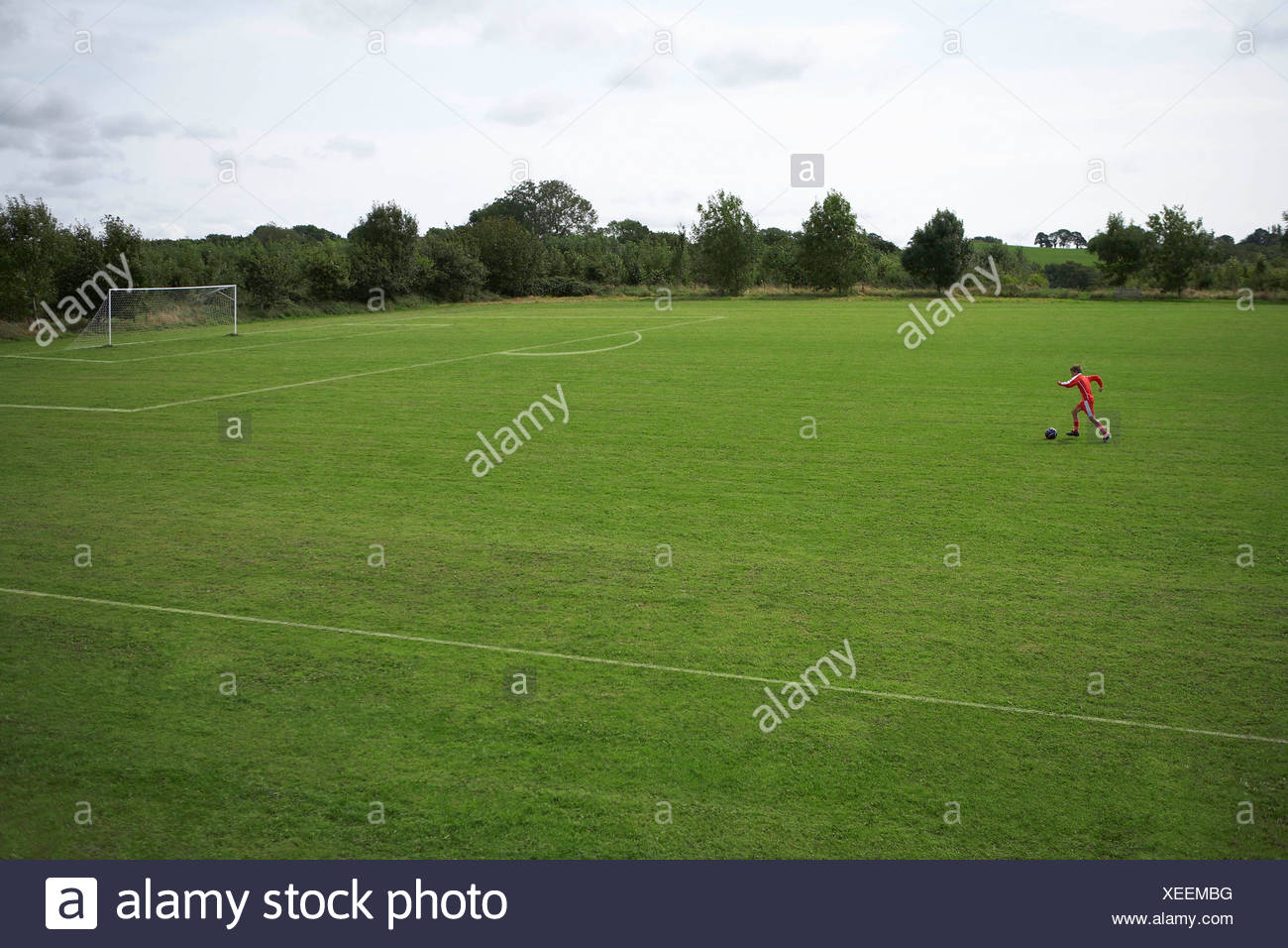 Footballer dribbling a ball towards goal - Stock Image