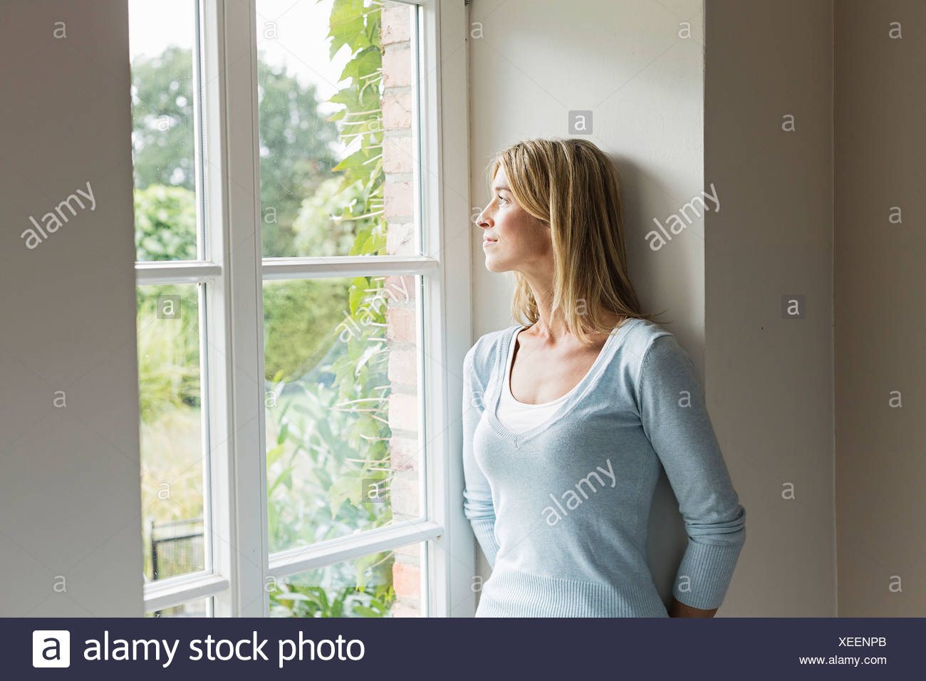 Portrait of mid adult woman looking out of window - Stock Image