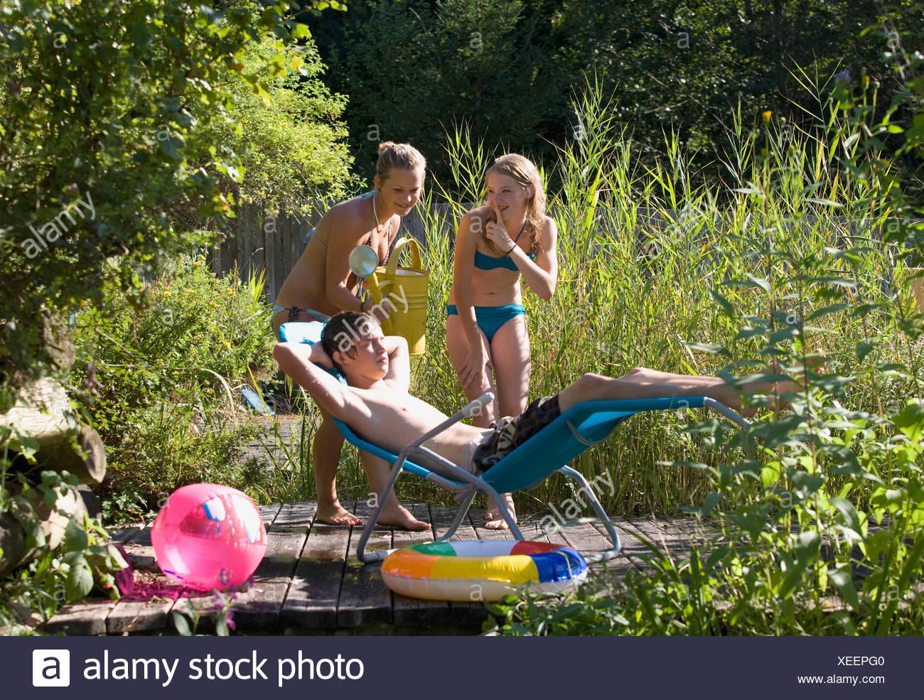 Austria, Salzburger Land, Teenagers (14-15) at garden pool - Stock Image