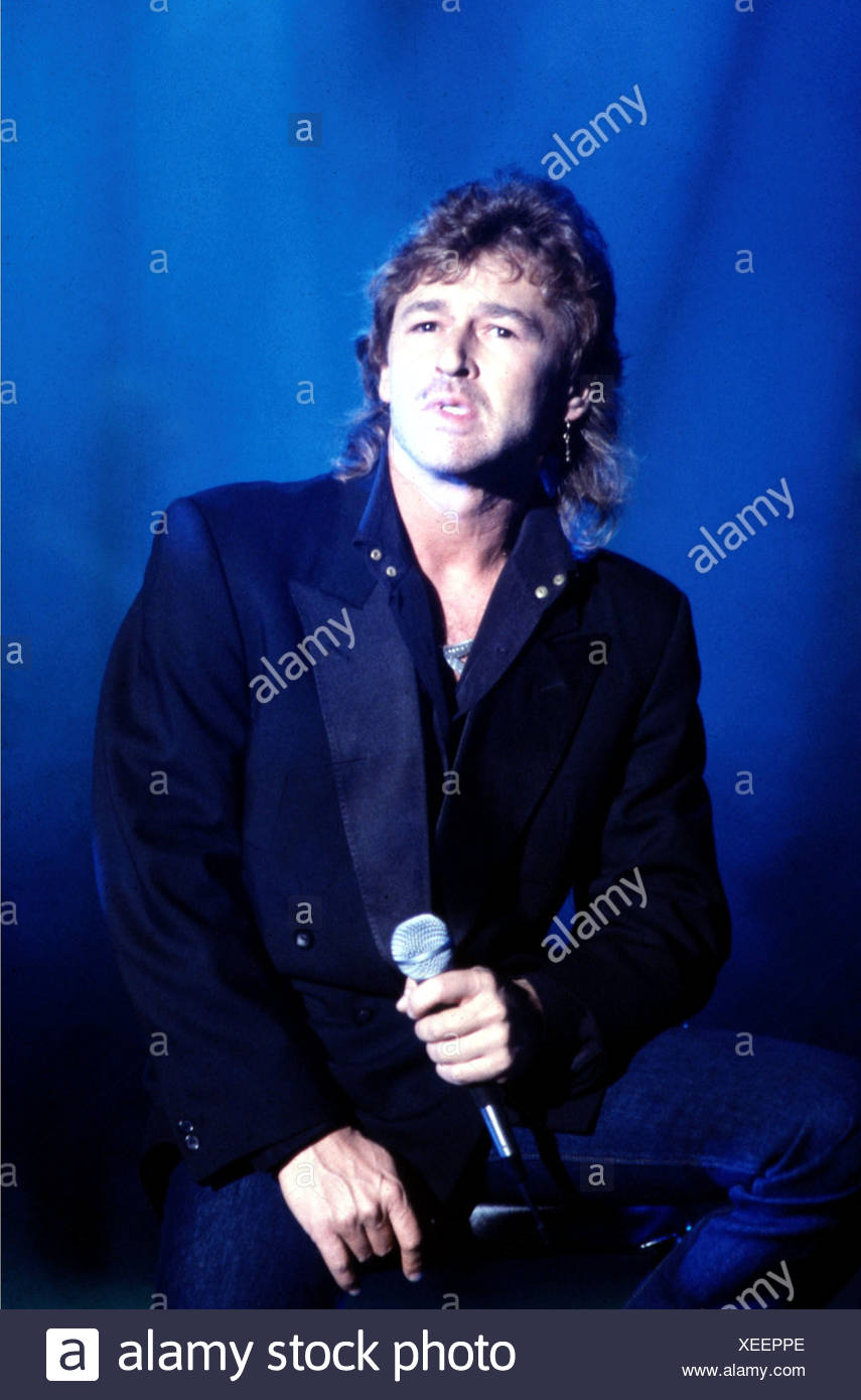 Maffay, Peter, * 30.8.1949, German singer, during a concert, 1980s, blue background, microphone, singing, - Stock Image