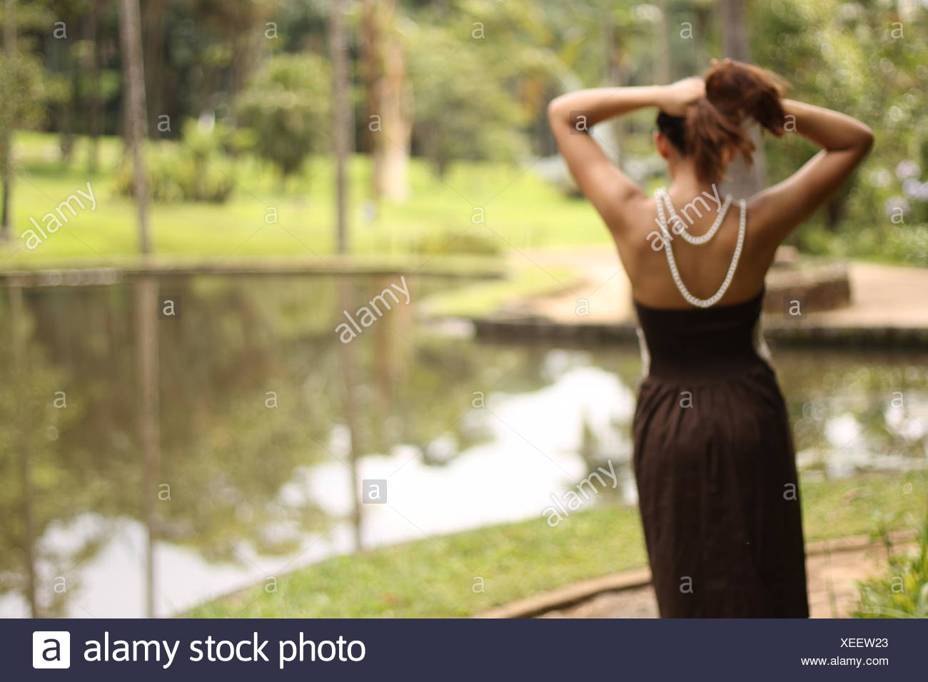 Rear View Of Woman Overlooking Countryside Lake - Stock Image