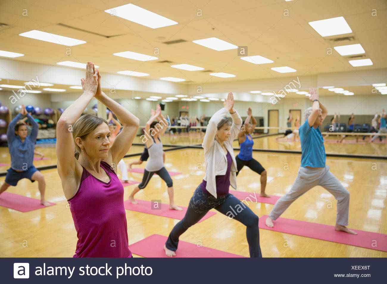 Group practicing crescent lunge in yoga class - Stock Image