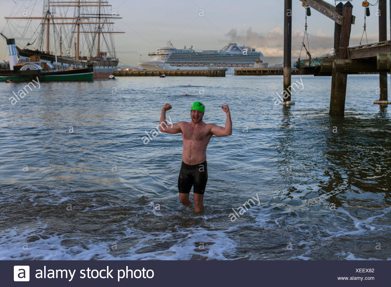 man in swimming trunks flexing muscles while standing in water, Dolphin Club, San Francisco, California, USA - Stock Image