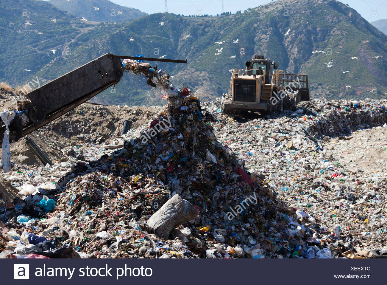 Machinery dumping waste in landfill - Stock Image