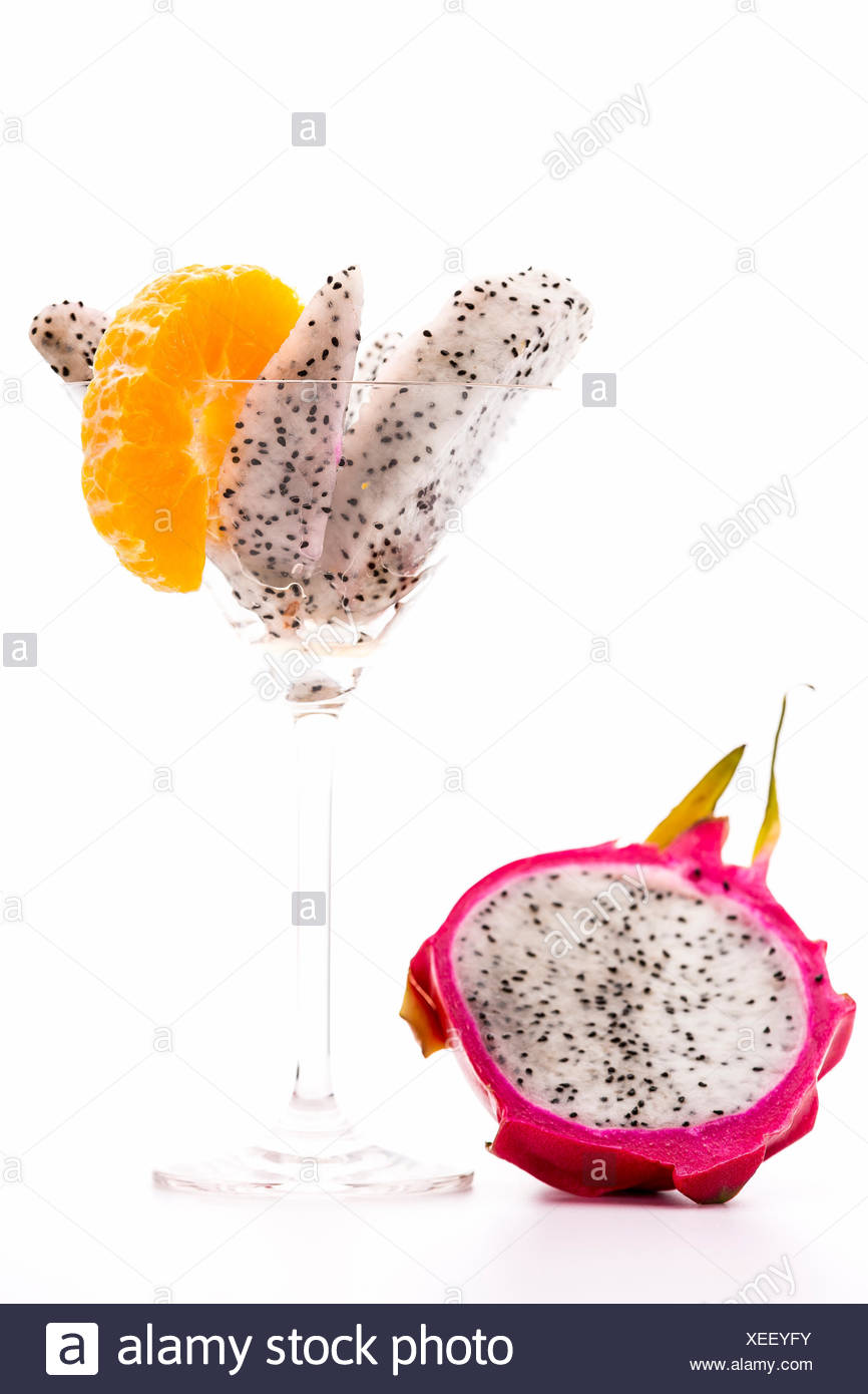 Wedges of the pitaya presented in a cocktail glass. A mandarine slice added for decoration. Next to it lies a halved pitaya. - Stock Image