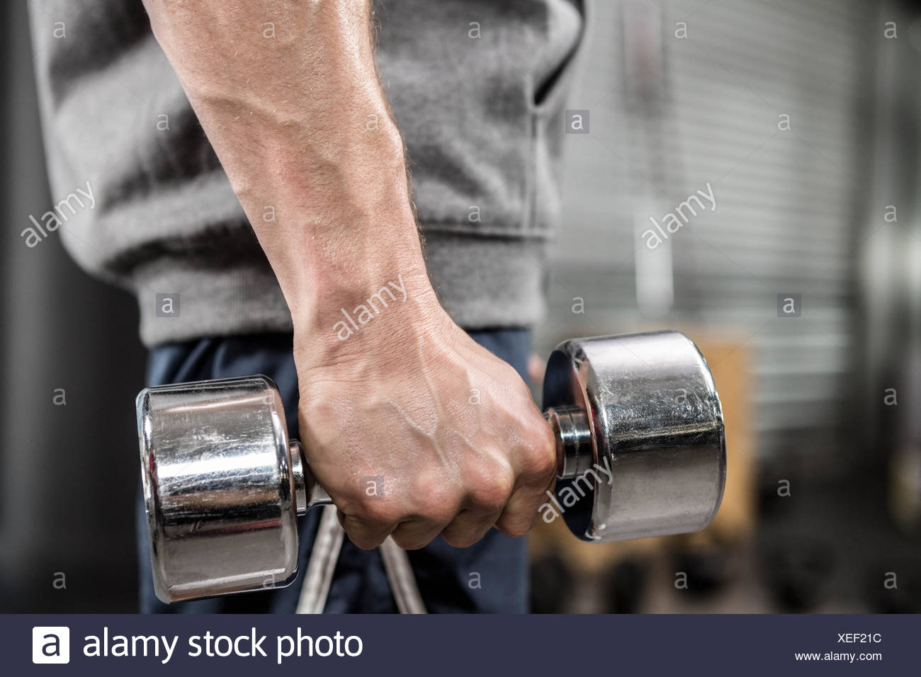 Muscular man with grey jumper holding dumbbell - Stock Image