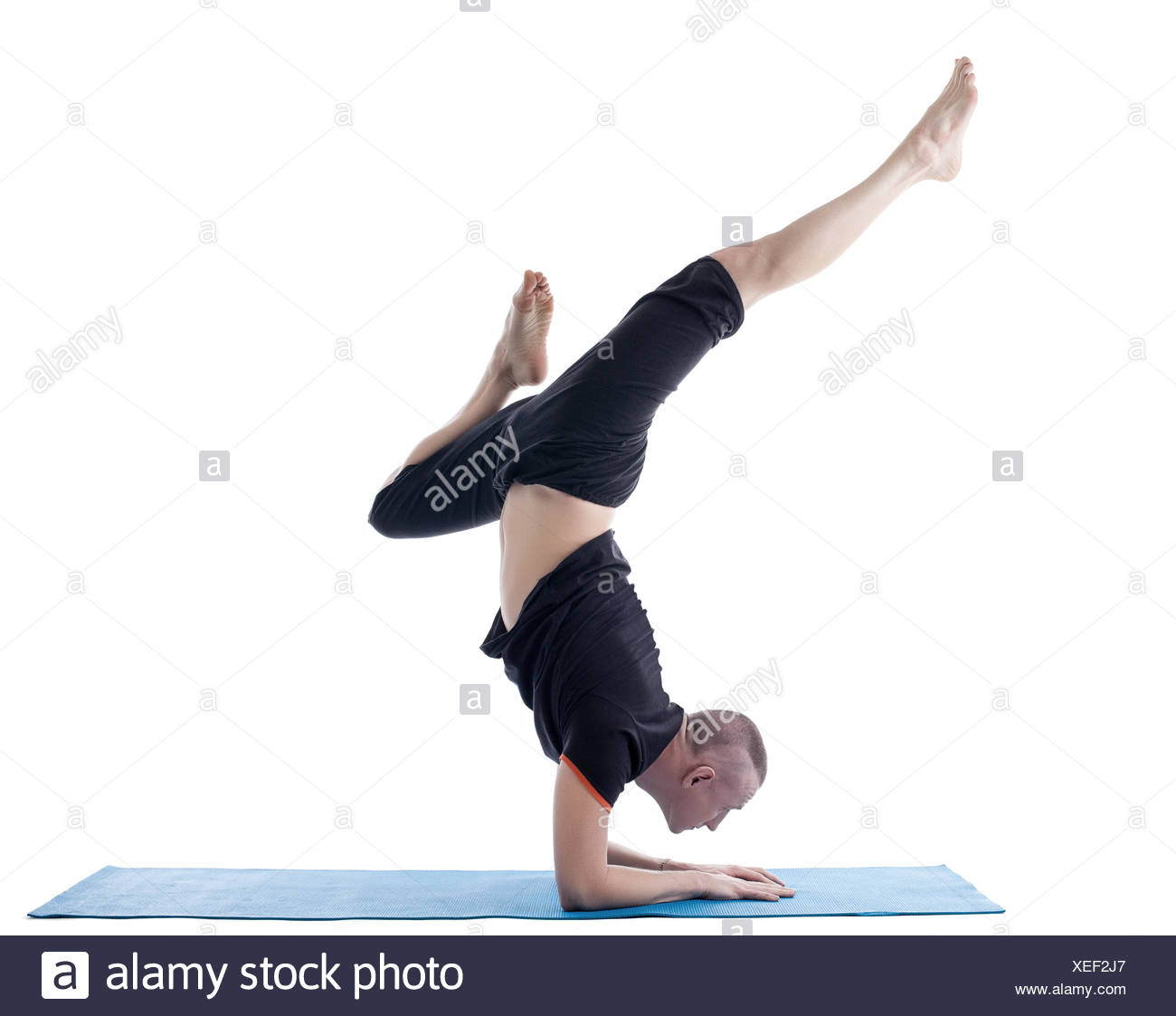 Flexible man posing in difficult yoga pose Stock Photo - Alamy