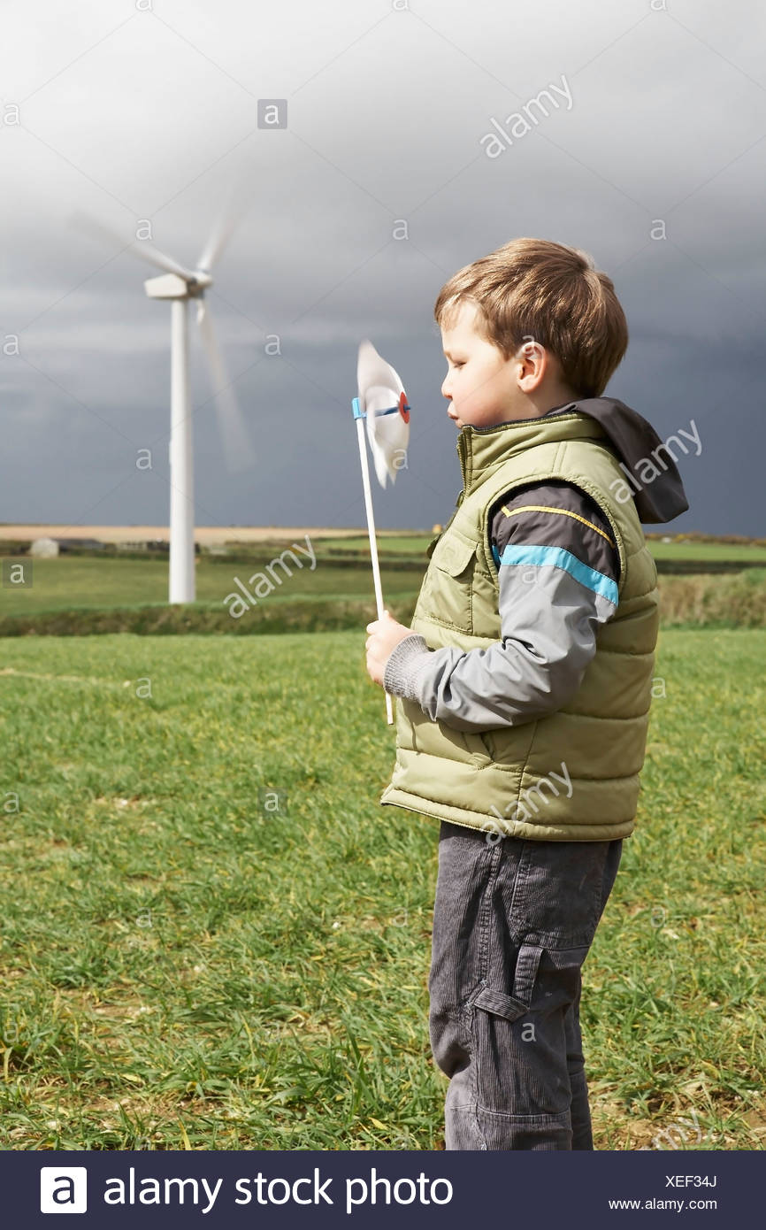 Boy blowing windmill on a wind farm - Stock Image