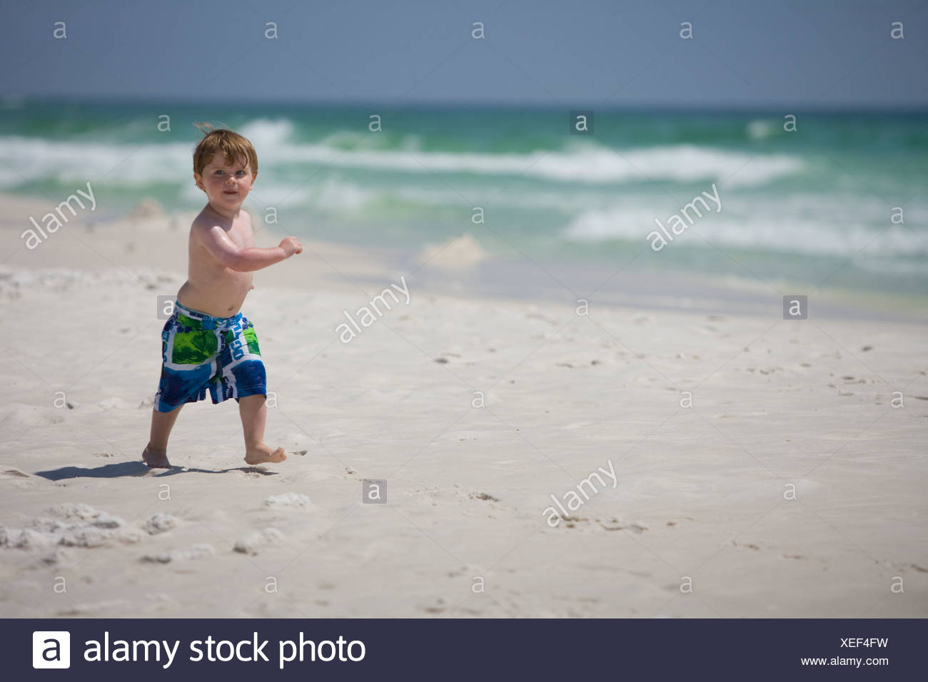 A little boy struts down the beach with the ocean in background. - Stock Image