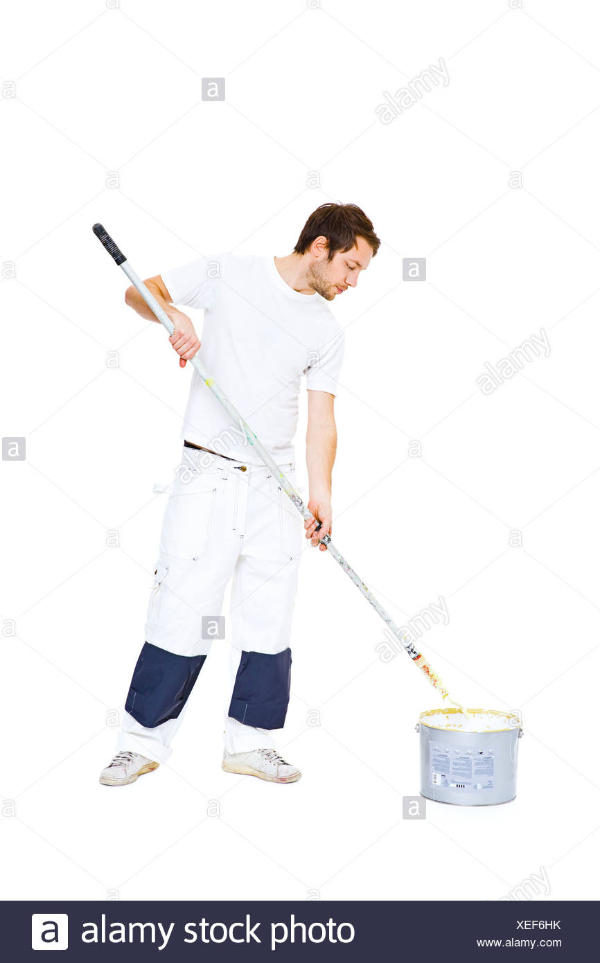 Studio shot of man with paint roller - Stock Image