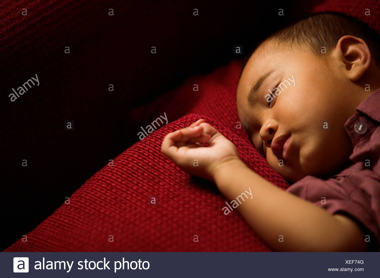 Asian toddler asleep on couch - Stock Image