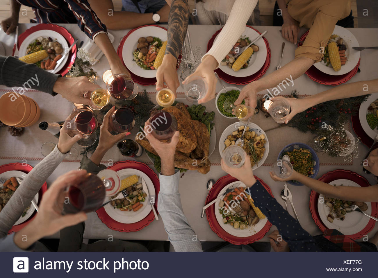 Overhead view family toasting wine glasses at candlelight Christmas turkey  dinner at table Stock Photo