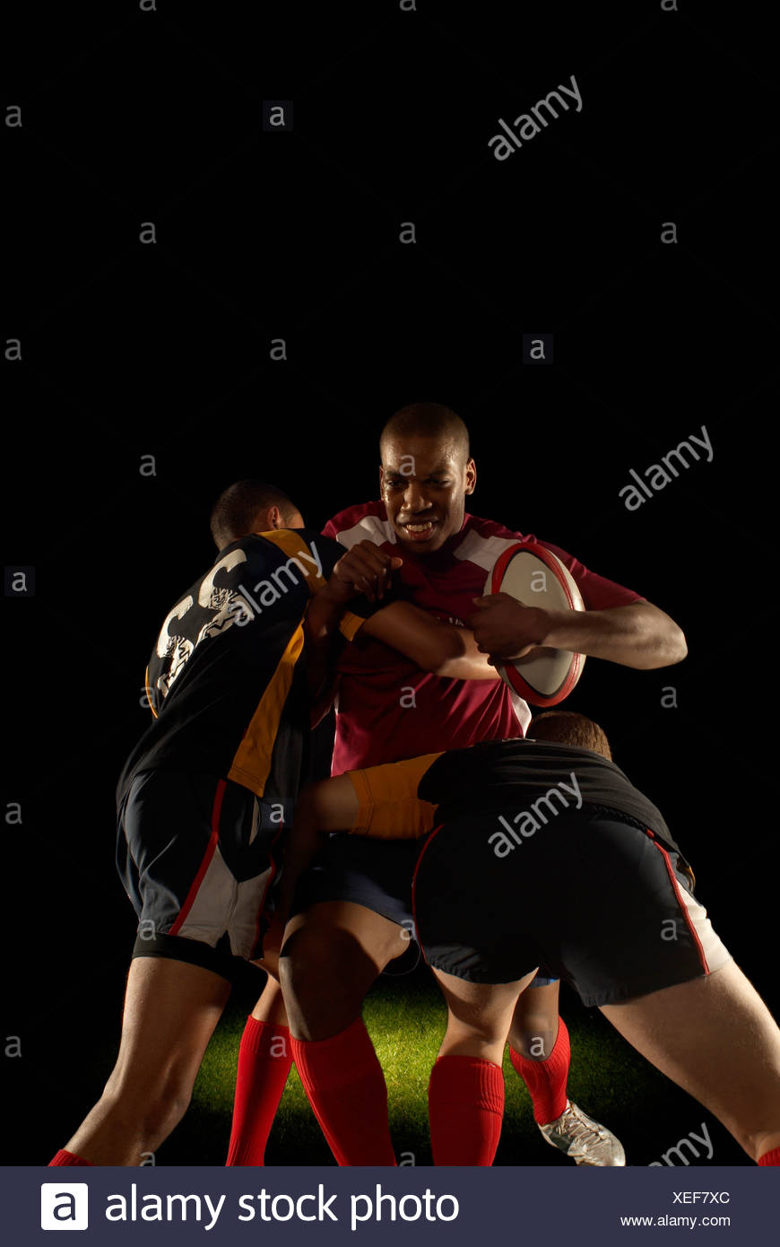 Two rugby players tackling one opponent - Stock Image