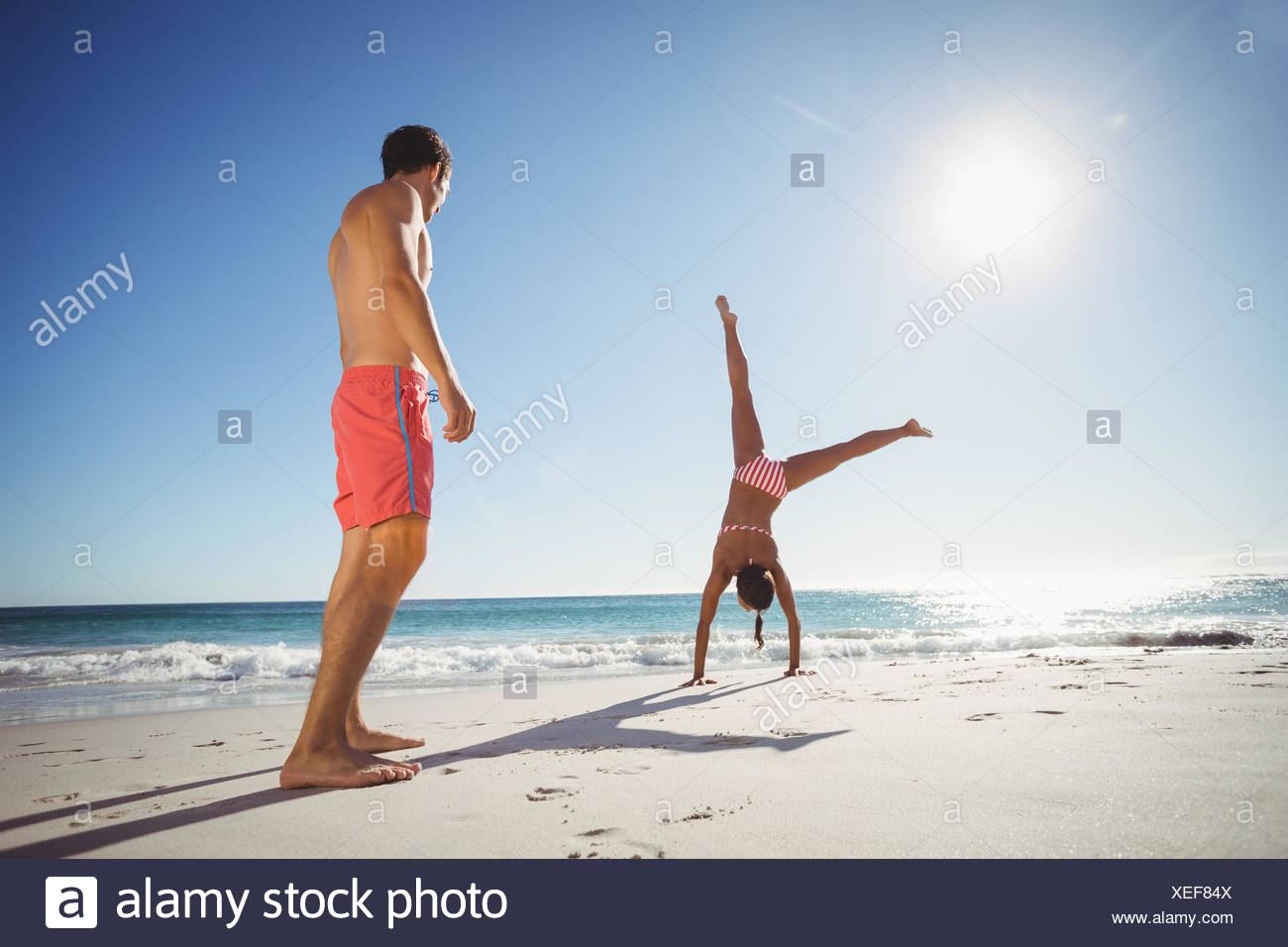 Woman performing somersault on beach - Stock Image