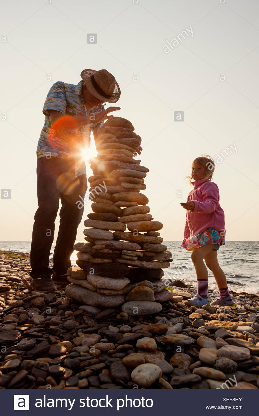 Sweden, Oland, Gronhogen, Grandfather and granddaughter (6-7) making stone heaps - Stock Image