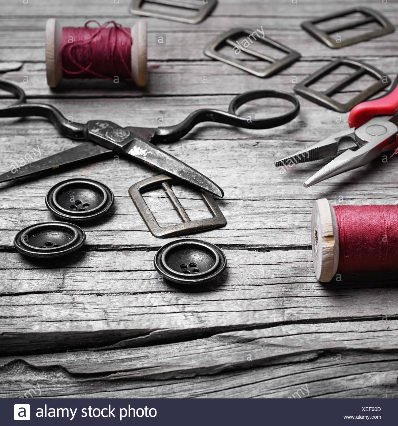 Buttons and fasteners from outdated clothes on wooden background - Stock Image