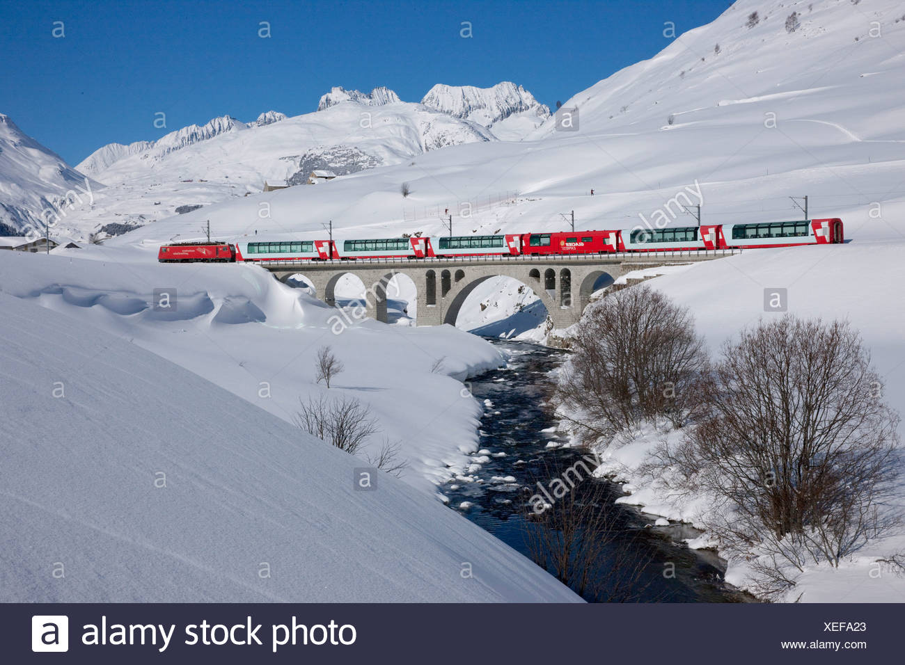 Switzerland Europe snow winter railway train railroad bridge canton UR Uri Ursenental Hospental Andermatt Glacier express brook - Stock Image