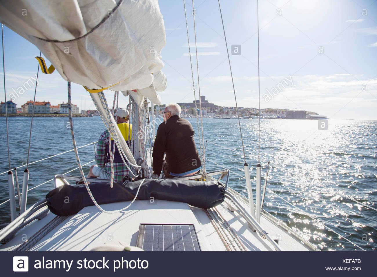 Sweden, Vastkusten, Bohuslan, Marstrand, Senior men sailing in bay - Stock Image