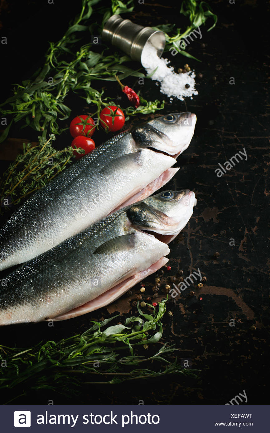 Tow raw fish seabass served with herbs, sea salt and cherry tomatoes on black wooden table - Stock Image