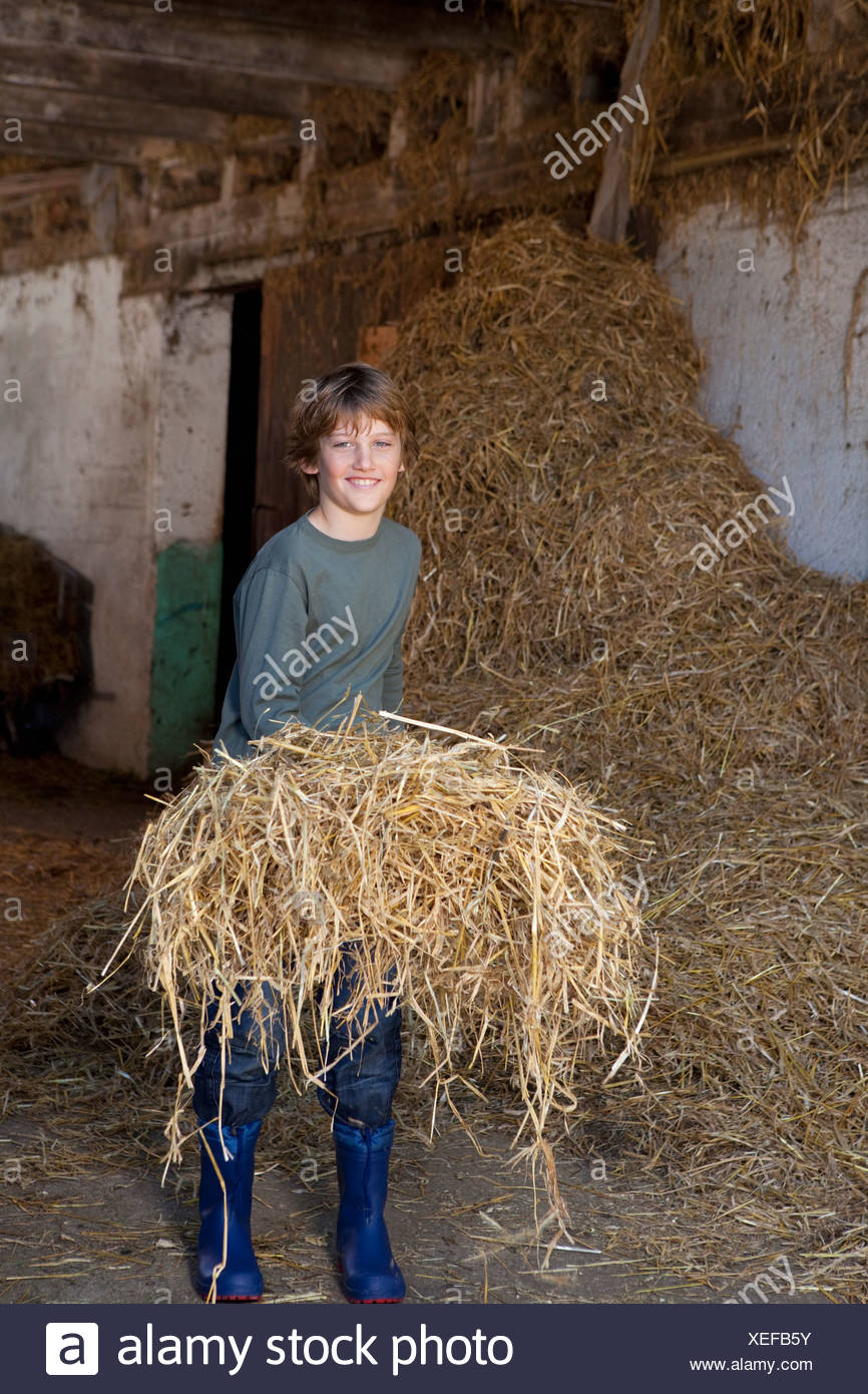 Boy with hay on fork, smiling - Stock Image
