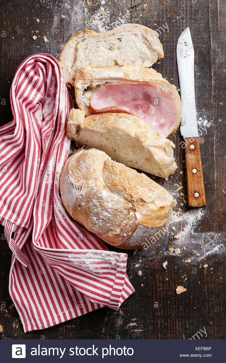 Fresh French bread with ham on wooden background - Stock Image