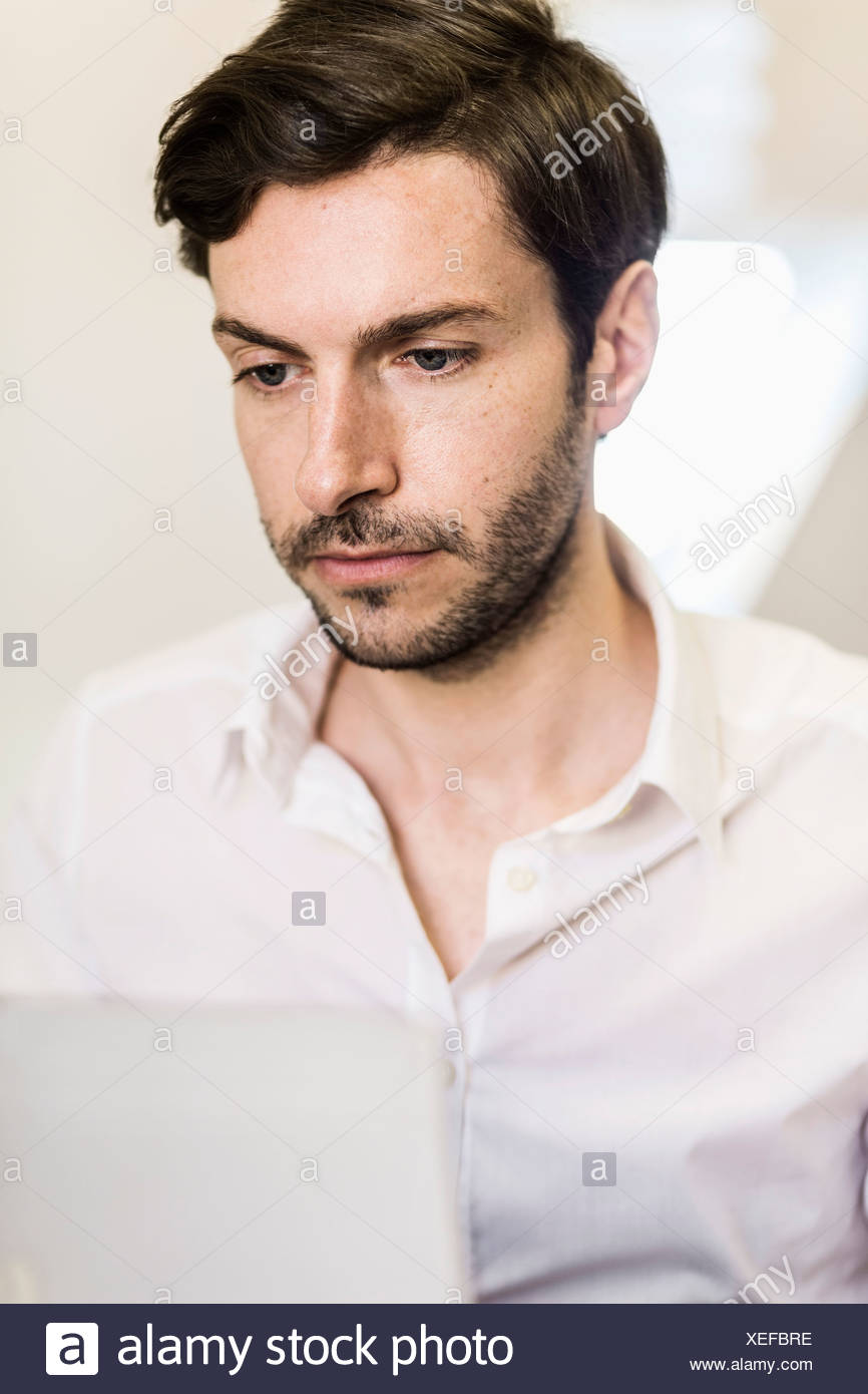 Businessman working on laptop in office - Stock Image