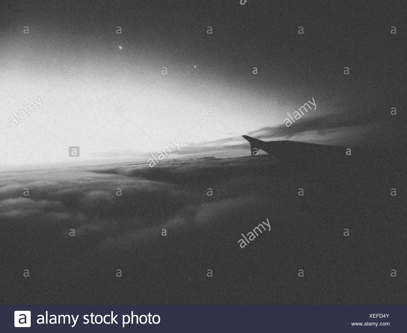Airplane Wing Flying Over Cloudscape - Stock Image